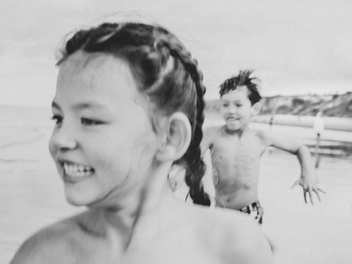 Happy siblings running at beach
