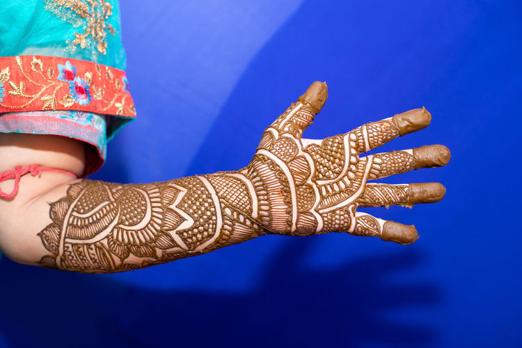 Cropped hand of bride with henna tattoo against blue background