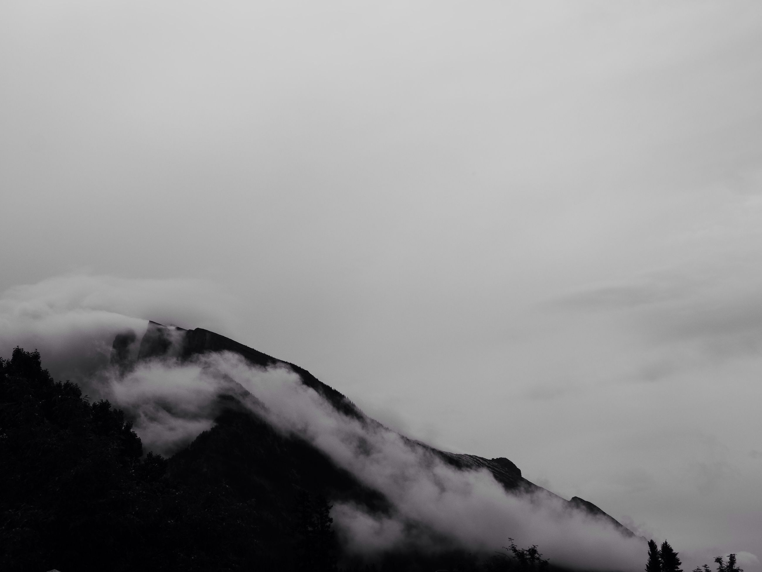 sky, tranquility, scenics, tranquil scene, beauty in nature, cloud - sky, weather, low angle view, nature, mountain, cloudy, tree, idyllic, overcast, cloud, outdoors, fog, silhouette, cloudscape, no people