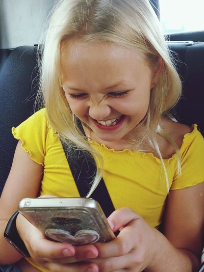 Close-up of girl holding mobile phone at home