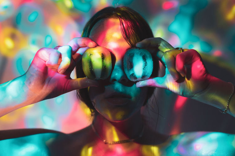 Colorful lights falling on young woman holding halved figs