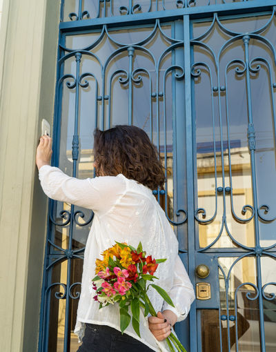 Back view photo of a girl holding a bouquet of flowers, in front of old iron door