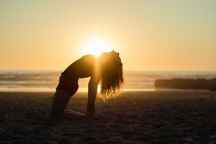 Woman Exercising On Beach During Sunset
