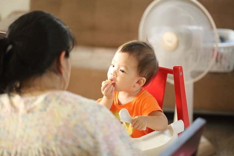 Rear view of mother against baby boy sitting on high chair at home