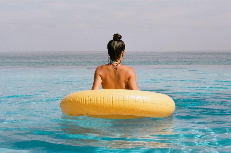 Rear view of shirtless man looking at sea