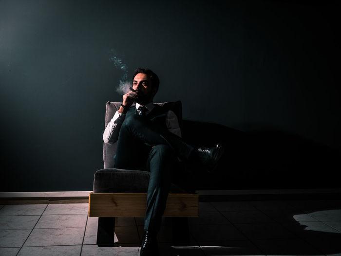 Man smoking cigar while sitting on chair at night