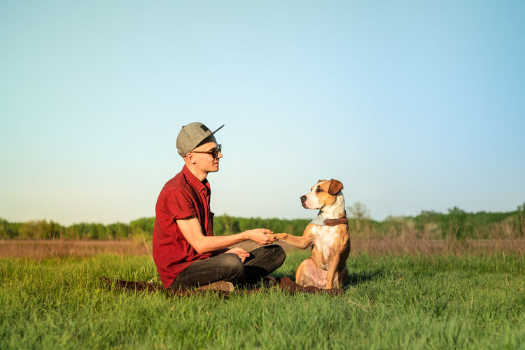 Young Man Shaking Hand With Dog While Sitting On Grassy Field Against Clear Sky