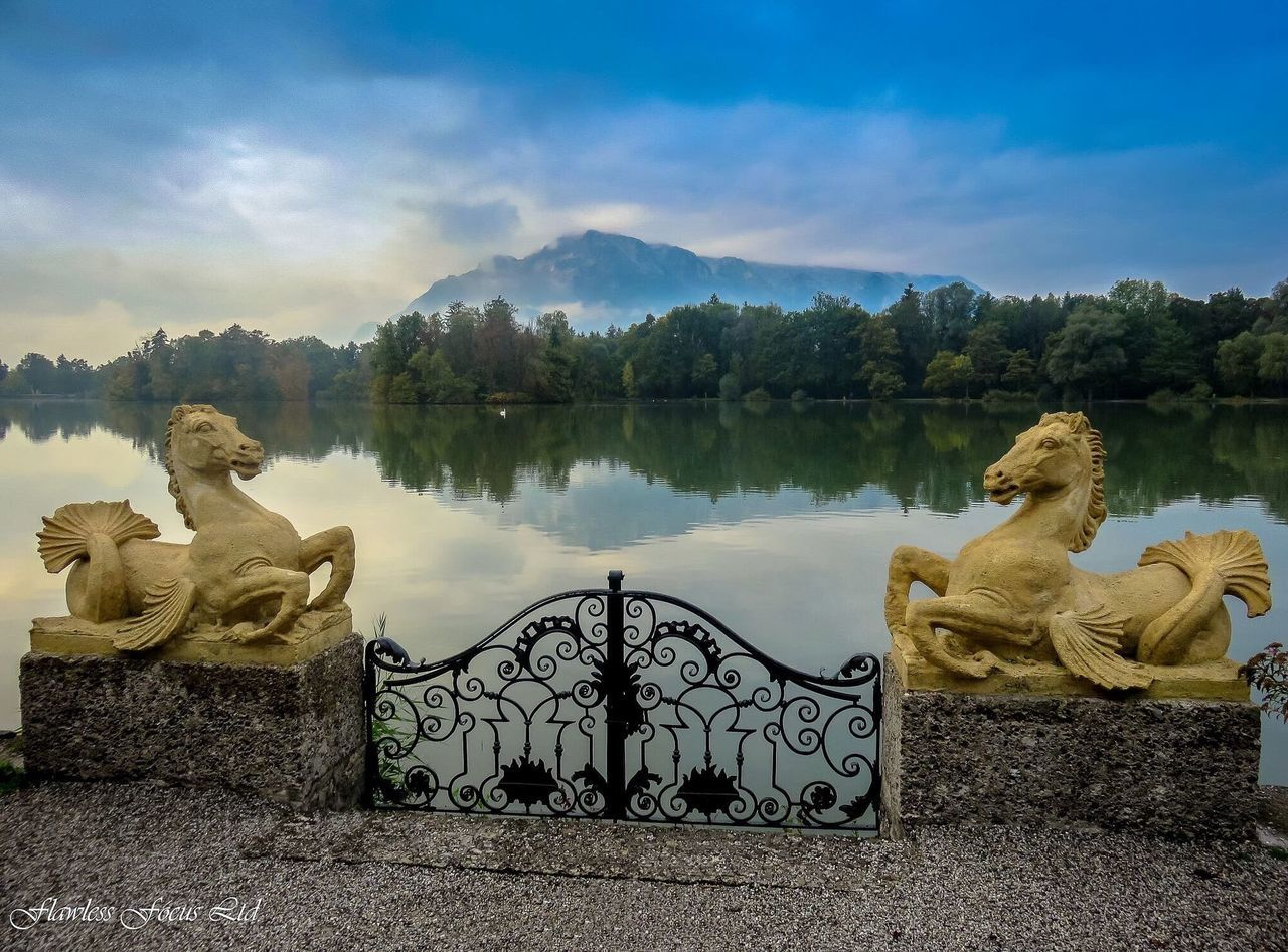 sky, cloud - sky, mountain, lake, outdoors, scenics, mountain range, nature, beauty in nature, day, no people, water, sitting, sculpture, tree