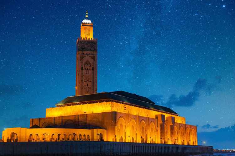 Illuminated historic mosque on sea against star field