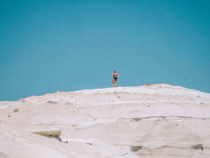 Low angle view of woman standing on white cliffs against blue sky