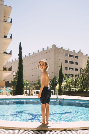 Full length portrait of shirtless man standing in swimming pool against clear sky