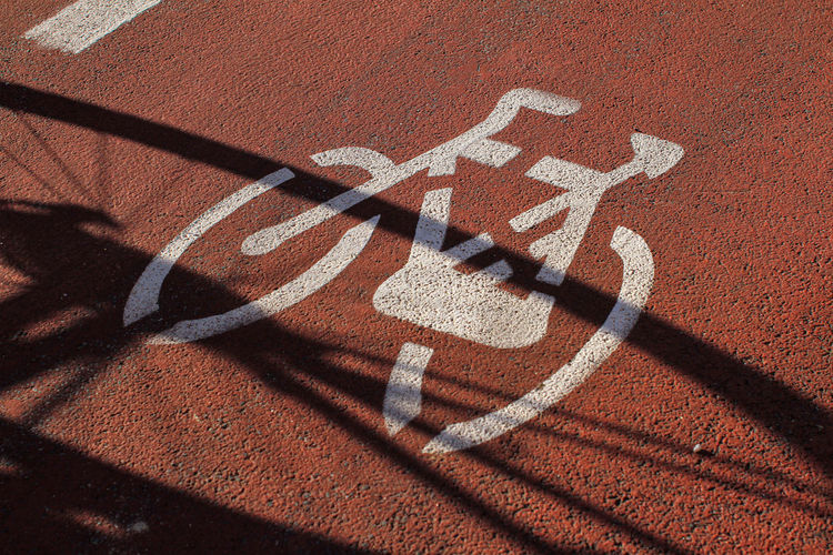 Signage on the cycle path, ocher-colored road surface, shadow of a bicycle.