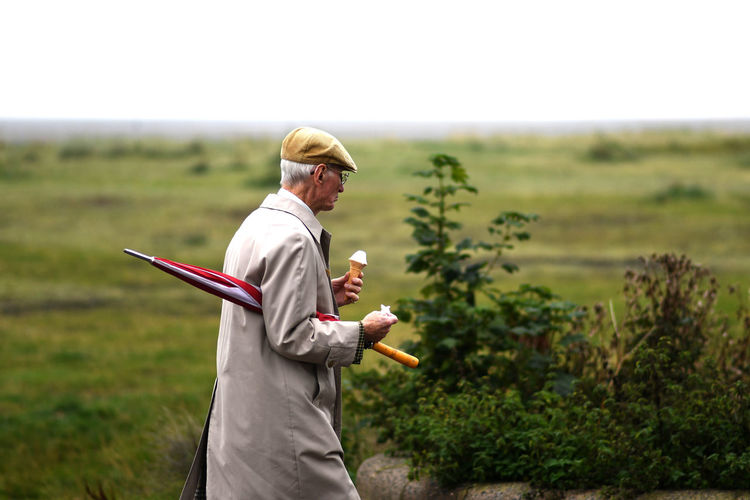 Old Man Beauty In Nature Day Environment Field Focus On Foreground Growth Holding Ice Cream Land Landscape Men Nature Non-urban Scene One Person Outdoors Plant Real People Side View Sky Standing Summer Three Quarter Length Umbrella