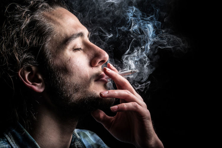 Close-up of young man smoking over black background