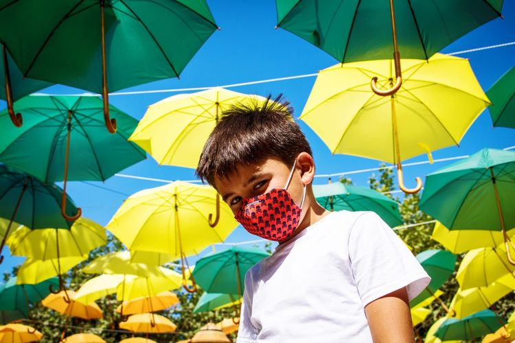 Low angle portrait of boy wearing flu mask standing against umbrellas