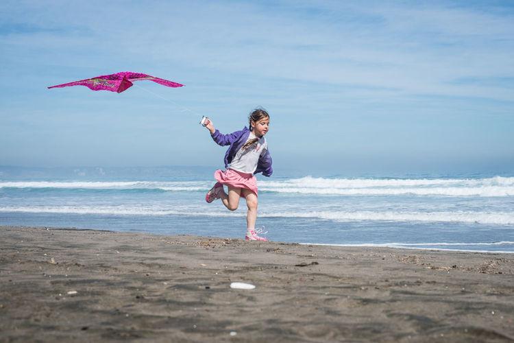 Full length of girl with kite running at beach against sky