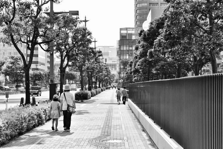 Rear view of people walking on footbridge in city