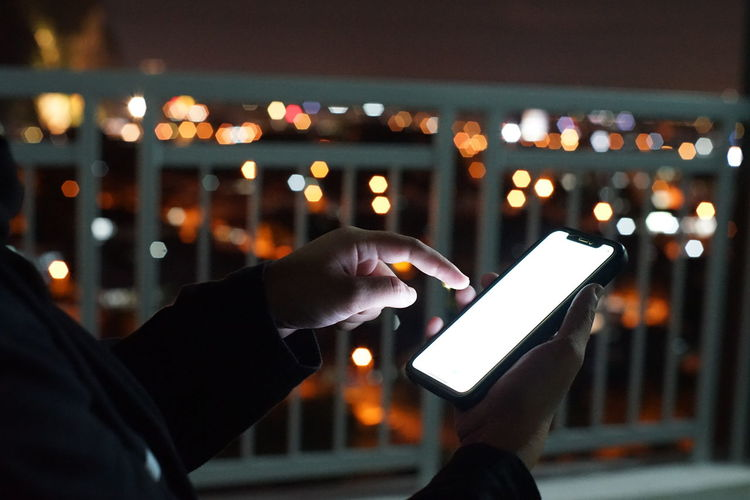 Man holding smart phone at night