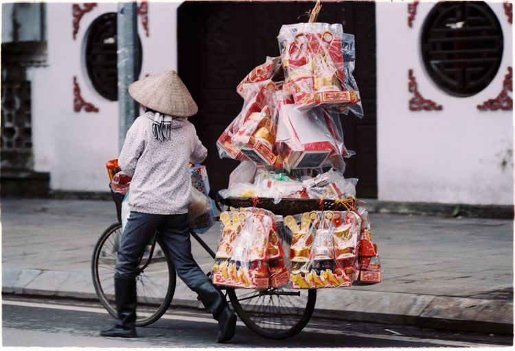 Rear View Of Street Vendor Carrying Toys On Bicycle