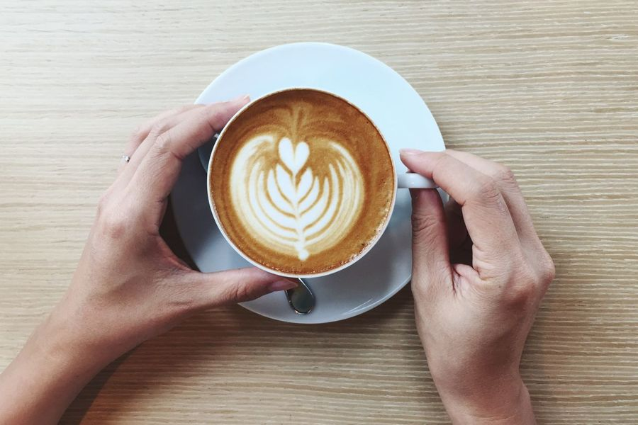 EyeEm Selects Human Hand Coffee - Drink Human Body Part Coffee Cup Drink Latte Latteart Froth Art Cappuccino Table Latte Refreshment Food And Drink One Person Directly Above Saucer Holding Wood - Material Indoors  Lifestyles Close-up