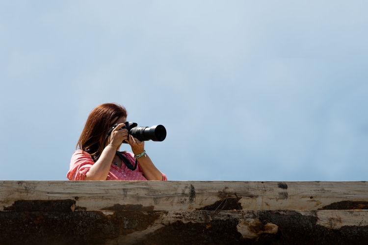Woman photographing against sky