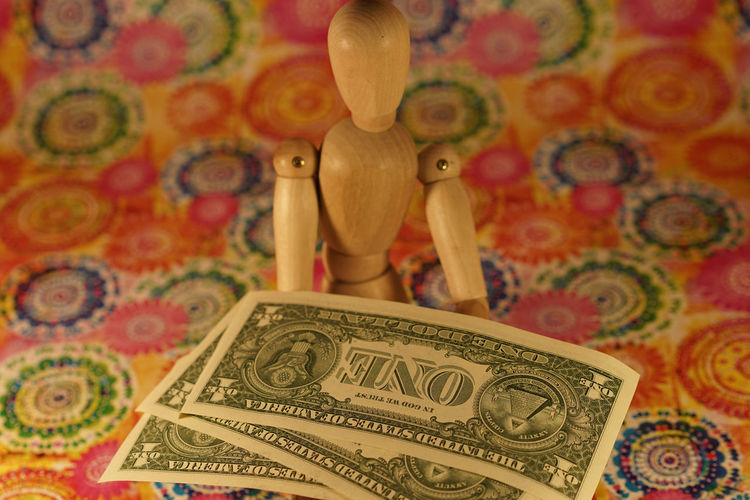 Wooden Figurine With Currencies On Designed Paper