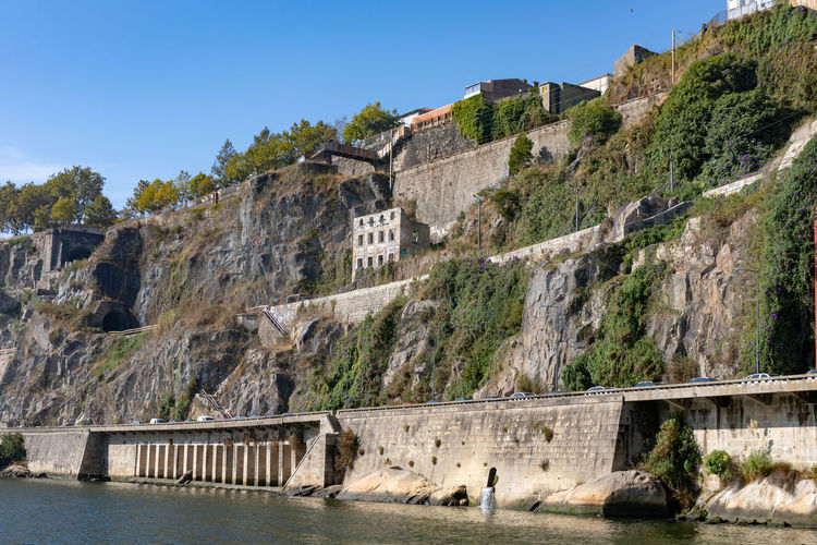 Cliffs on banks of river Douro in Porto Architecture Bridge Building Exterior Built Structure Dam Day Fuel And Power Generation History Mountain Nature No People Outdoors Rock Scenics - Nature Sky Tourism Travel Travel Destinations Tree Water