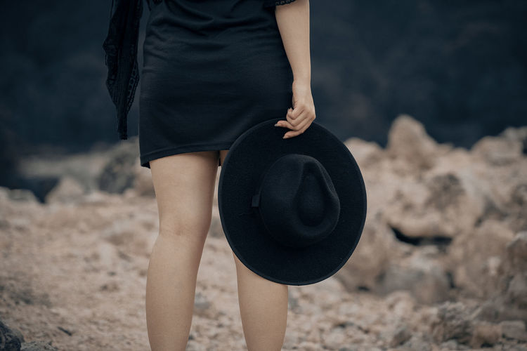 Midsection of woman holding hat while standing on land