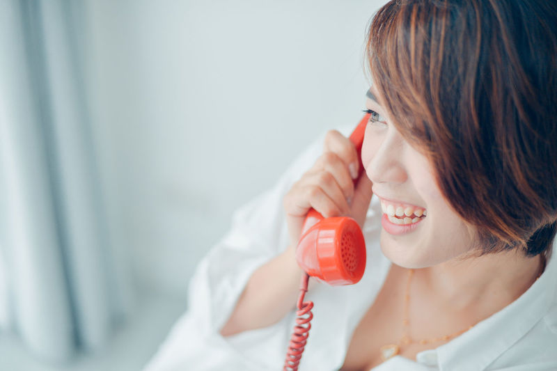 Close-up of smiling woman talking on telephone