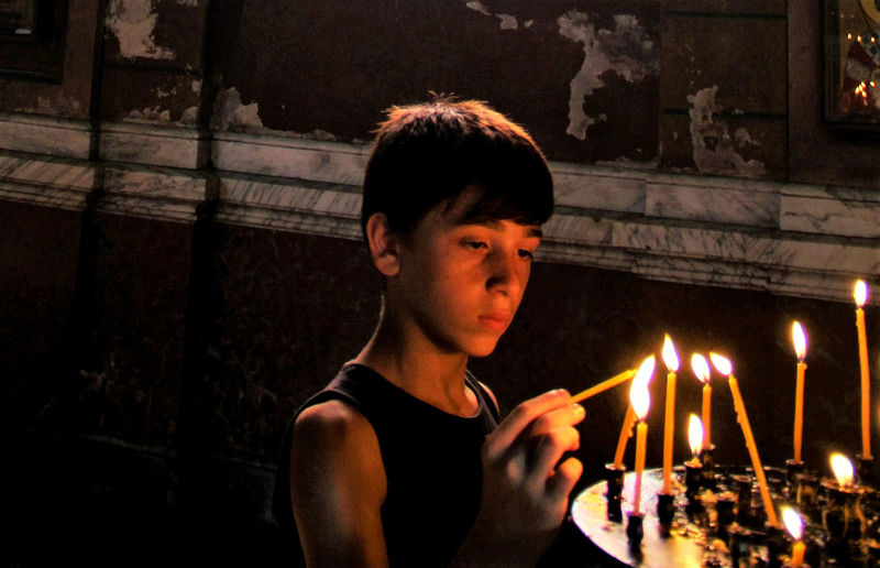 Turning to God at the altar Candles Close-up Darkness And Light Face Focus On Foreground Illuminated Lifestyles Portrait Prayer The Light Up Close Street Photography Telling Stories Differently The Street Photographer - 2016 EyeEm Awards The Magic Mission