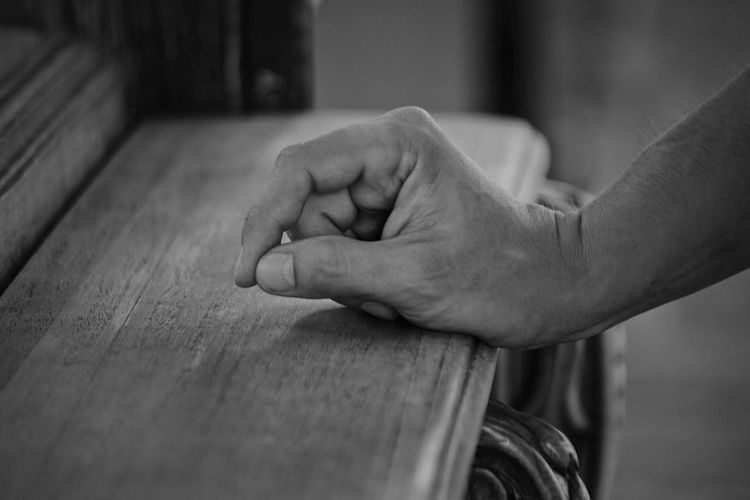 Close-up of man hand on wood at home