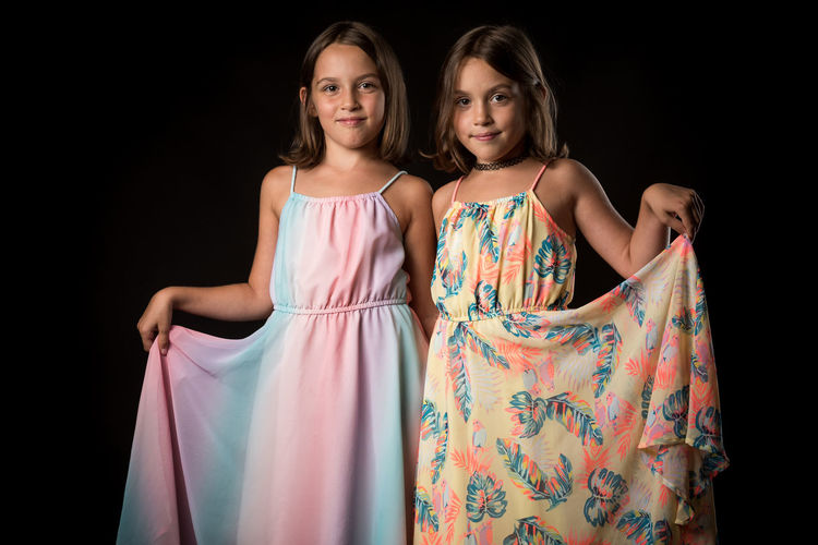 Portrait of girl standing with sister against black background