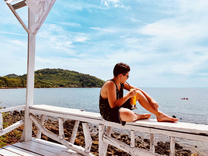 Boy drinking juice in glass while sitting on railing by sea against sky