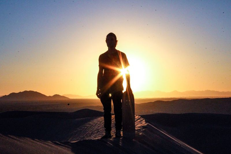 Silhouette Man Standing With Sandboard In Desert During Sunset