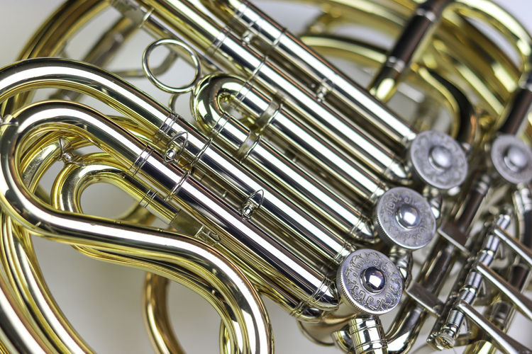Music Instrument French horn Metal Musical Instrument Music No People Close-up Indoors  Brass Instrument  Arts Culture And Entertainment Gold Colored Shiny Focus On Foreground Still Life Brass Musical Equipment Silver Colored Detail Studio Shot White Background Wind Instrument Sheet