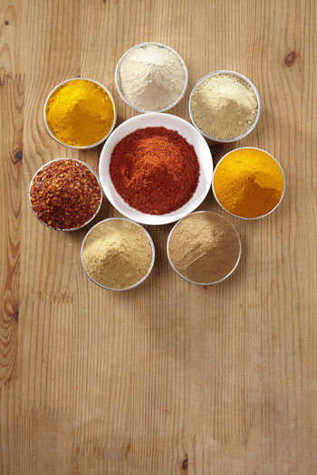 Aluminum container filled with colorful spices Chili Pepper Choice Curry Food And Drink Hot Red Spicy Aroma Assortment Cinnamon Colorful Cumin Directly Above Flavor Food Ground - Culinary Ingredient Paprika Pepper Seasoning Spice Turmeric  Variation Wooden Background Yellow