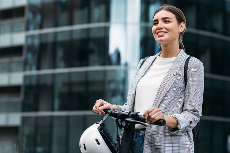 Mid adult woman standing by bicycle in city