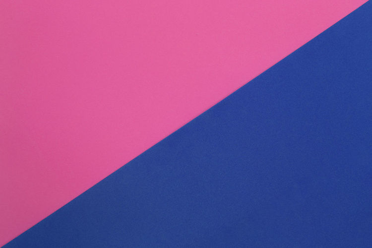 Low angle view of pink wall against blue sky