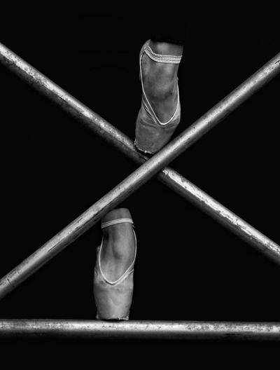 Low section of ballet dancer climbing on railing against black background
