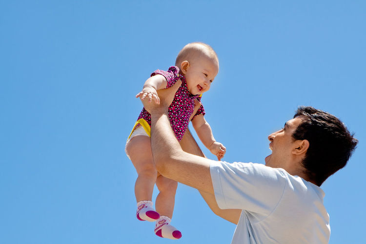 Low angle view of father playing with baby against clear blue sky