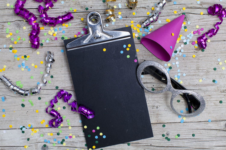 Close-up of multi colored confetti and clipboard on table