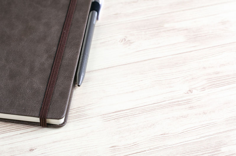 Mockup closed diary with pen on wooden background.selective focus shot, Wood - Material Indoors  Pen No People Table Close-up High Angle View Writing Instrument Education Still Life Book Black Color Two Objects Wood Diary Publication Brown Simplicity Business Wood Grain Blank Fountain Pen