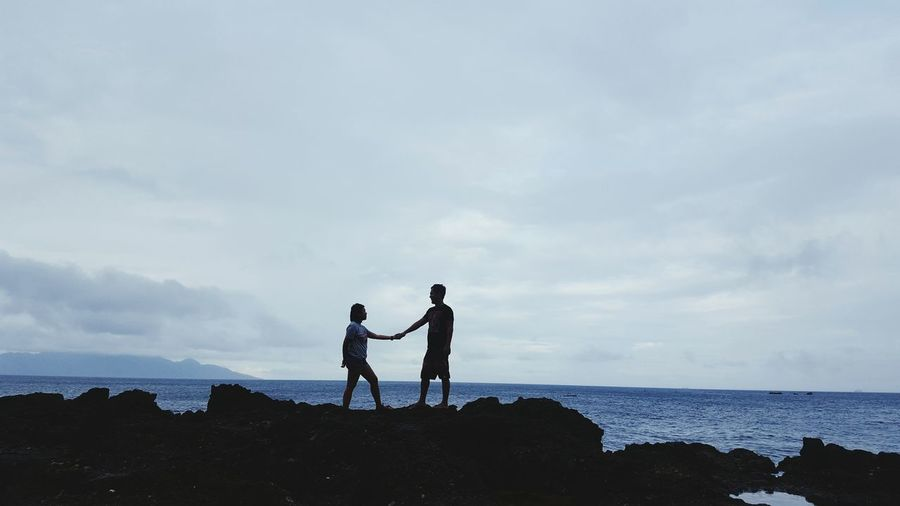 Man and woman standing on rock formation by sea against sky