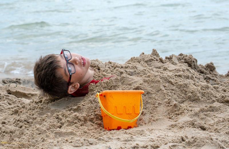 Boy lying down on sand at beach