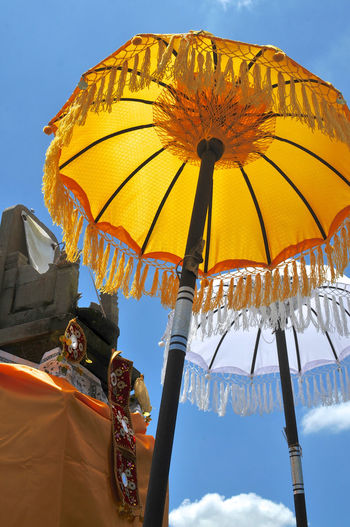 Low angle view of two typical balinese umbrellas placed in front of a small shrinein ubud, bali