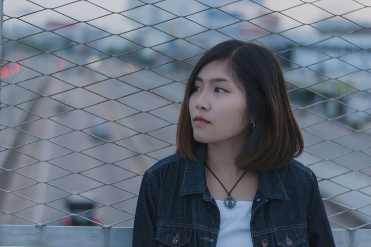 Young woman standing against chainlink fence
