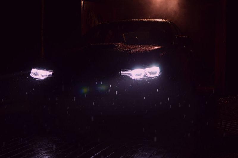 Illuminated lights seen through wet windshield at night