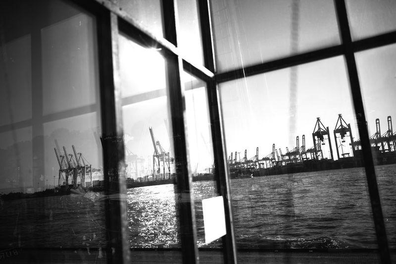 Sailboats in sea seen through window
