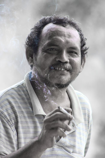 Portrait of smiling man smoking cigarette