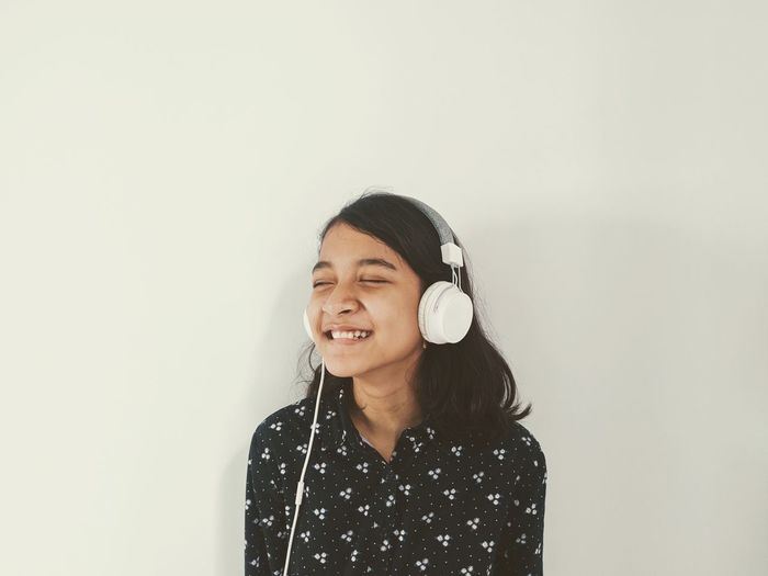 Smiling young woman standing against wall and listening to the music from headphone